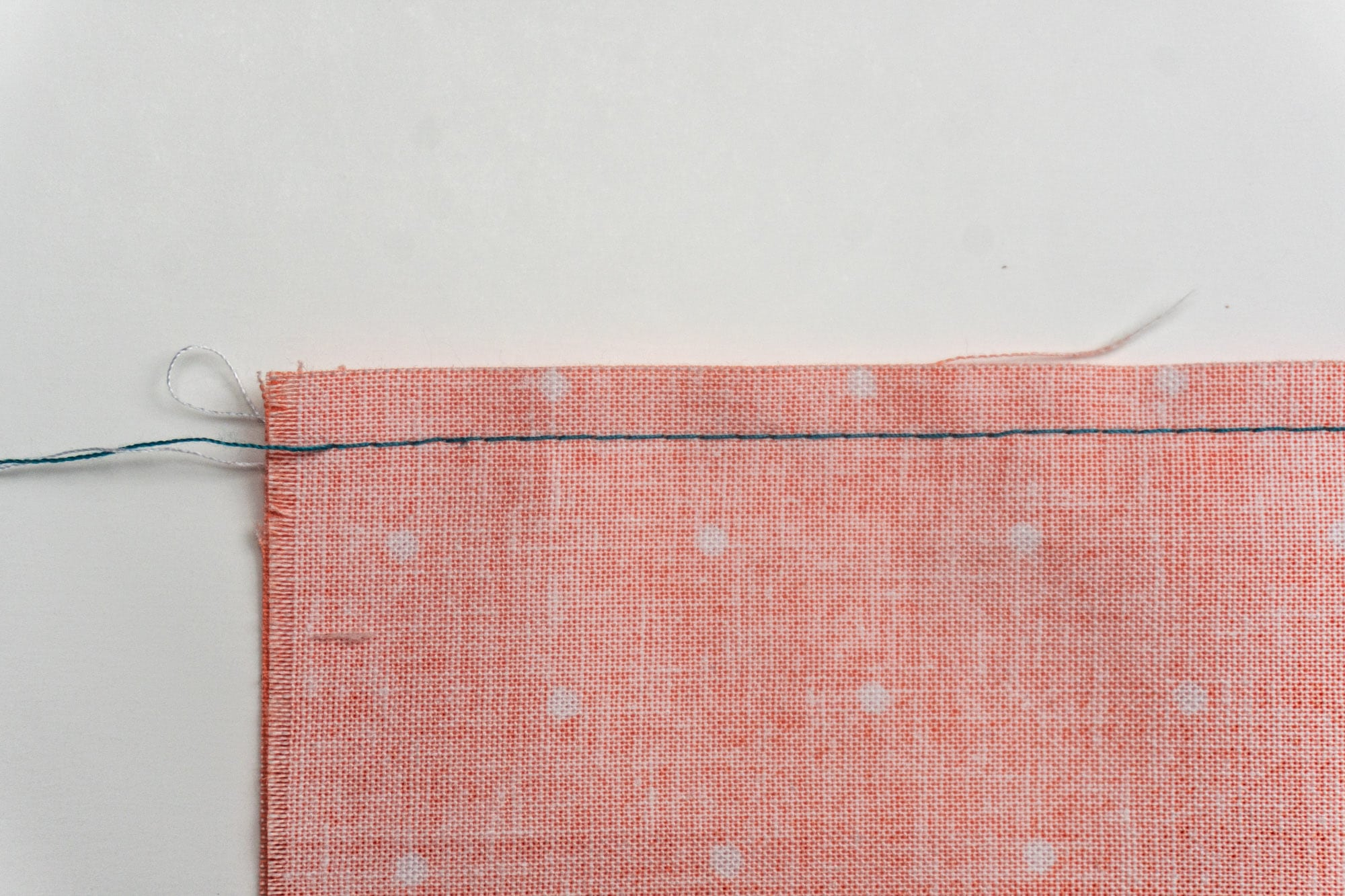 Teal straight stitch on the wrong side of coral fabric.