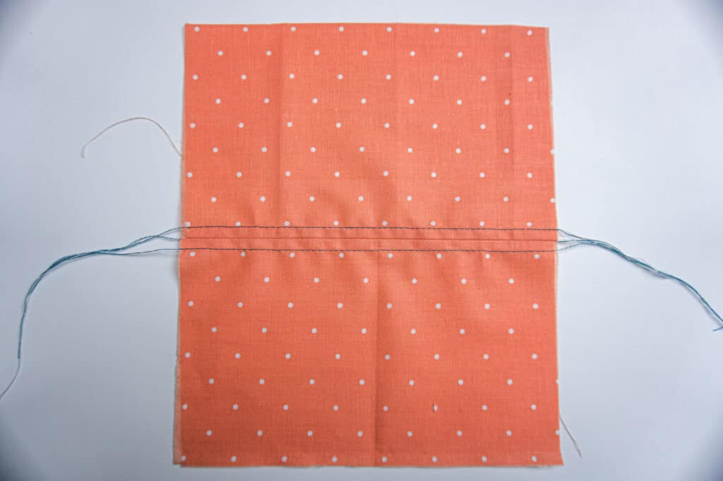 Coral coloured fabric with two rows of top stitching running parallel to seam.