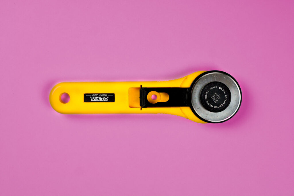A bright yellow Olfa rotary cutter loaded with a blade.