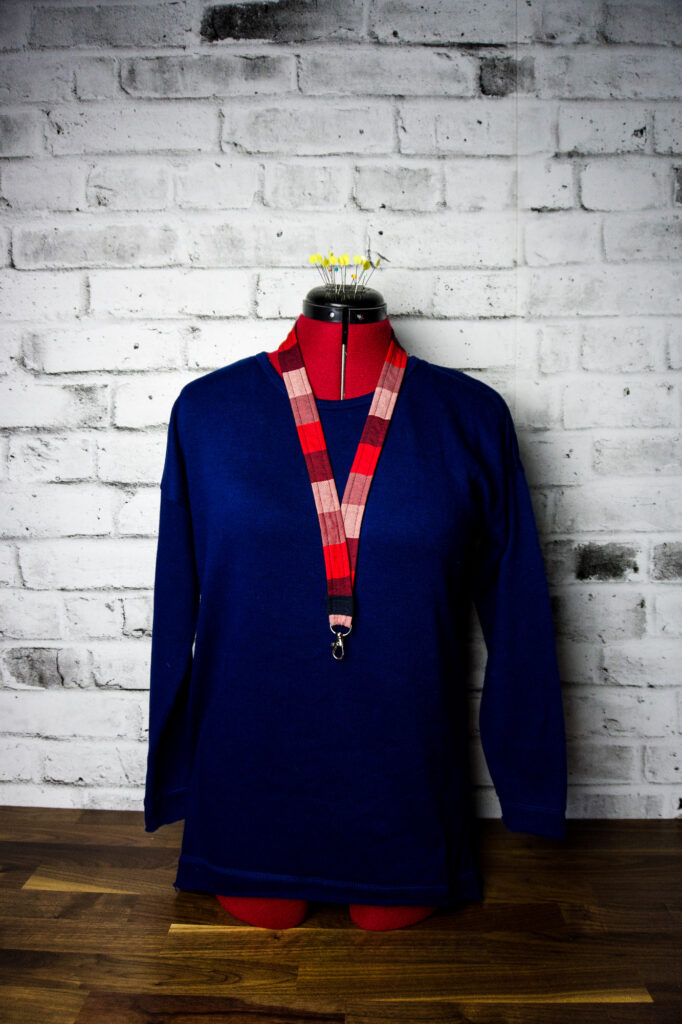 A dress manikin in a royal blue sweater wearing a plaid diy lanyard.