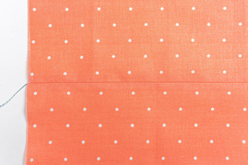 Coral fabric that has been sewn together with a straight stitch and pressed open.