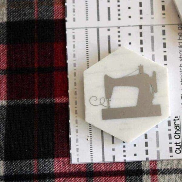 A hexagon tile with a sewing machine decal holding a pattern on fabric.